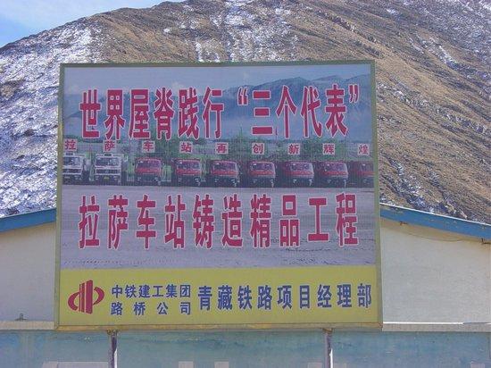 """""""Dach Świata ucieleśnieniem trzech reprezentacji, Dworzec Lhaski projektem wzorowym. Chińska Grupa Budowy Kolei oraz firma Luquiao, Zarząd Projektu Linii Qinghai-Tybet"""". Wedle teorii """"trzech reprezentacji"""" byłego sekretarza partii komunistycznej i prezydenta ChRL Jiang Zemina partia reprezentuje całe społeczeństwo – w gruncie rzeczy już kapitalistycznych – Chin. Idea ta ma także odzwierciedlać rosnące znacznie sektora prywatnego w tworzeniu miejsc pracy i dostatku; w 2002 roku wpisano ją do statutu Komunistycznej Partii Chin"""
