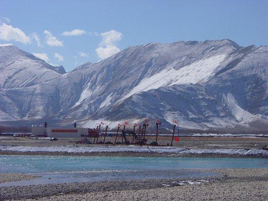 """Prowizoryczny stalowy most na Kjiczu w południowo zachodniej części Lhasy. Napis na budynku: """"Tymczasowy sztab budowy drogi szybkiego ruchu"""". Chińscy robotnicy przejęli większość etatów dla robotników wykwalifikowanych; dla Tybetańczyków zostały nisko opłacane prace fizyczne"""